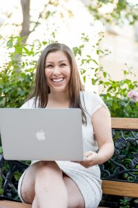 woman sitting on bench outside with laptop in her lap, smiling