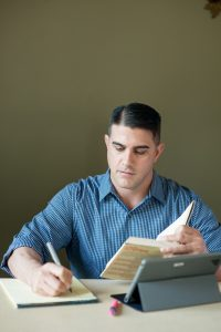 man studying at table with book and pen